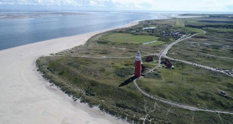 Strand op Texel met uitzicht op vuurtoren