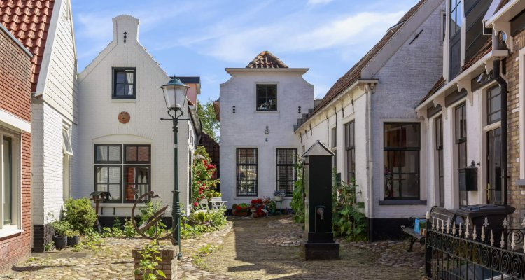 Old and picturesque houses, buildings and architecture typical in downtown Den Burg village on the wadden island Texel on a sunny day in Summer