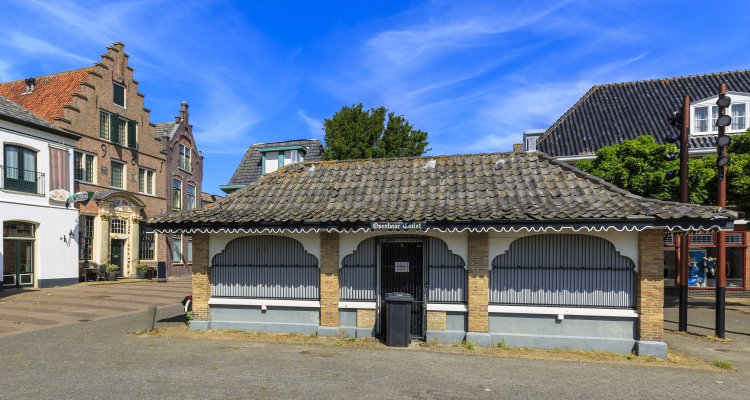 Public restroom, old and picturesque houses, buildings and architecture typical on a shopping street in Den Burg on the wadden island Texel during a sunny day in Summer