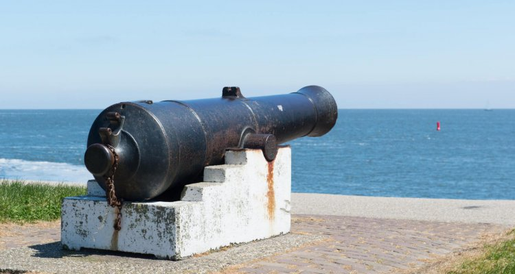 Old metal cannon at sea